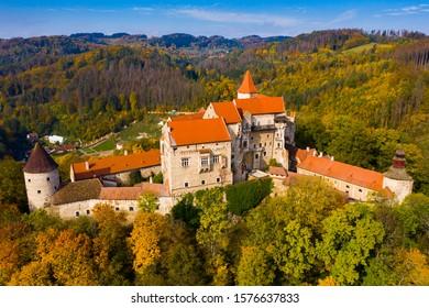 Picturesque autumn landscape with imposing historic Pernstejn Castle on rock above village of Nedvedice, Czech Republic
