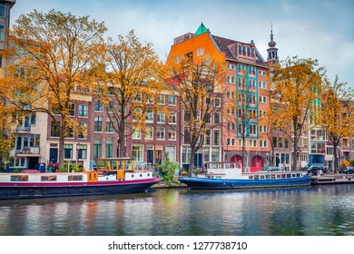 Picturesque autumn scene of Amsterdam city. Famous Dutch channels and great cityscape. Colorful morning landscape in Netherlands, Europe. Traveling concept background.