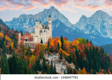 Picturesque autumn view on Neuschwanstein Castle with colorful trees and the Alps on background, Bavaria, Germany. Beautiful autumn colorful scenery.