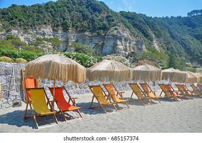 The picturesque beach on the Italian island of Ischia - the mountains, white sand, beach umbrella and sunbeds