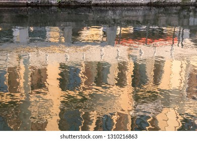 picturesque blurred reflection of old facades in Naviglio canal water,  shot in bright winter light at Milan, Lombardy,  Italy