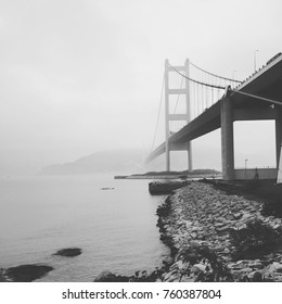 Picturesque bridge in black and white disappearing in the cold foggy rainy morning
