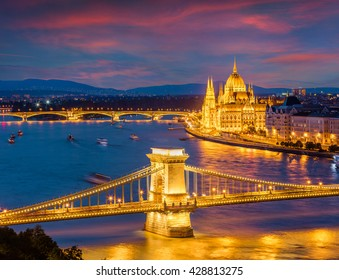 Picturesque cityscape of Hungarian parliament building with famous Chain Bridge on the Danube river. Dramatic spring  sunset in Budapest, Hungary, Europe. Artistic style post processed photo.