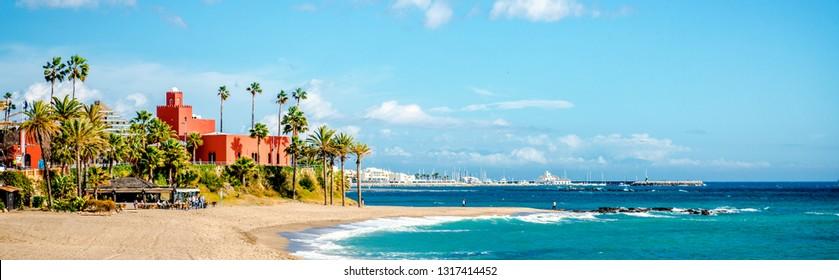Picturesque coast turquoise bay of Mediterranean Sea blue sky, palm trees orange famous landmark Bil Bil Castle on the coast, port, horizontal view of Benalmadena resort town. Malaga, Andalusia, Spain