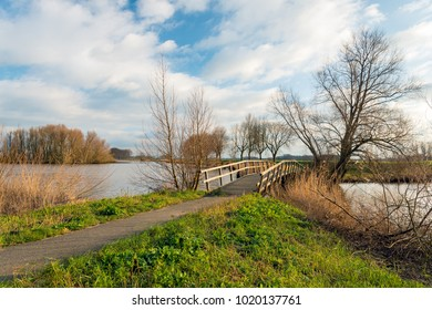 Picturesque and colorful landscape with a wooden bridge over the water of a small lake in the Netherlands. It is a sunny day with a cloudy sky in the winter season.