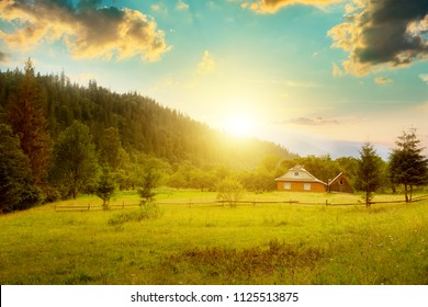 Picturesque countryside in mountains. Small house on slope Carpathians at sunset.
