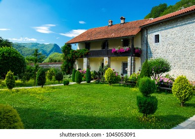 Picturesque courtyard of the monastery of Moraca with green grass lawn, flowers and buildings with red tiled roofs in front of blue sky, Montenegro