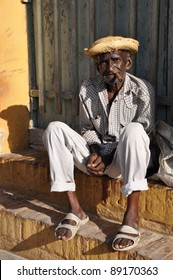 Picturesque Cuban old man is on one of the streets of Trinidad, with hat and cigar