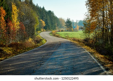 Picturesque fall colors and beautiful autumn country road in Finland. Bright fall colors and beautiful autumn country road in Finland. Colorful fall leaves on the trees. Traveling in concept.