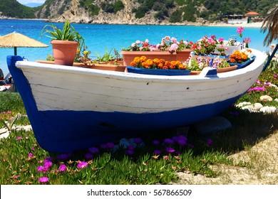 Picturesque fishing boat with flowers at Alikes beach, Ammouliani island, Halkidiki