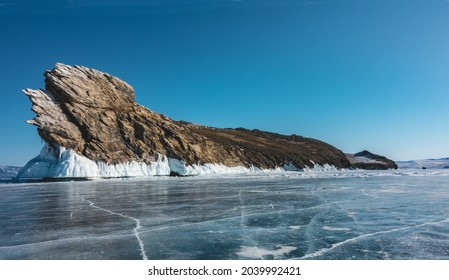 A picturesque granite rock, devoid of vegetation, rises above a frozen lake. Whimsical outlines against the blue sky. A layer of icicles on the base. Cracks on the ice. Baikal