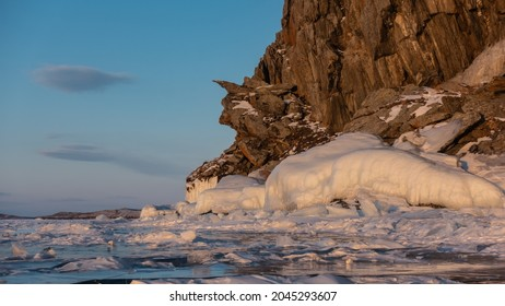 A picturesque granite rock, devoid of vegetation. Fancy outlines. At the foot there is a layer of icicles. Sparkling ice floes are scattered on the frozen lake. Blue sky. Evening golden hour. Baikal