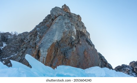 A picturesque granite rock, devoid of vegetation, against a clear azure sky. Steep gray-brown slopes, bizarre outlines. At the base are blocks of blue ice hummocks. Baikal