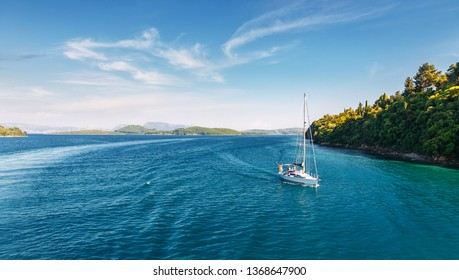 Picturesque Greece landscape with yacht during sunset. Wonderful colorful seascape. Sailing ship yachts with white sails at opened sea