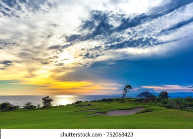 A picturesque green golf course on the background of the sea and the blue sky, in the clouds of which shines a sunny orange light. Sunset on Jimbaran, South Kuta, Bali, Indonesia.