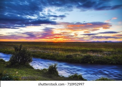 Picturesque landscape of a mountain river with traditional nature of Iceland at amazing sun set.