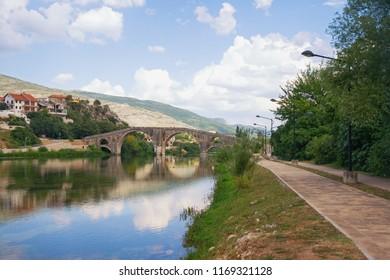 Picturesque landscape with old stone bridge. Bosnia and Herzegovina, view of Trebisnjica river, embankment of Trebinje city  and Arslanagic ( Perovic ) Bridge