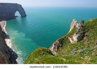Picturesque landscape on the cliff of Etretat. la Manneporte natural rock arch wonder, cliff and beach. Coast of the Pays de Caux area in sunny spring day. Etretat, Normandy, France.