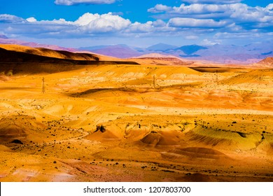 Picturesque landscape with orange sand dunes and mountains in Sahara desert with bright blue sky and clouds in Morocco