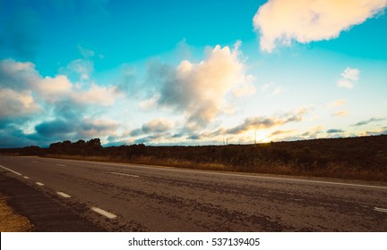 Picturesque landscape scene and sunset above road