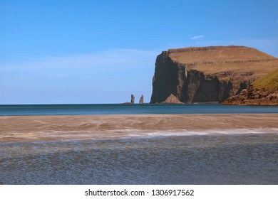 Picturesque landscape with spectacular view to legendary sea stacks Risin og Kellingin (The Giant and the Witch). Glorious sceneries of the Faroes. Postcard motif.