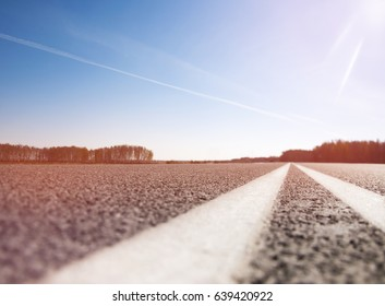 The picturesque landscape and the Sunrise over the road. Asphalt road with marking. With the blur.