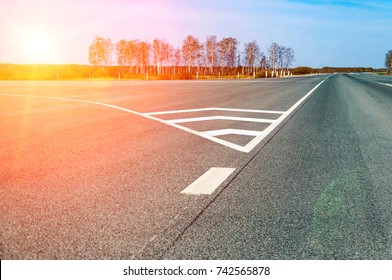 The picturesque landscape and the Sunrise over the road. Asphalt road with marking. With the blur and bright sunlight.