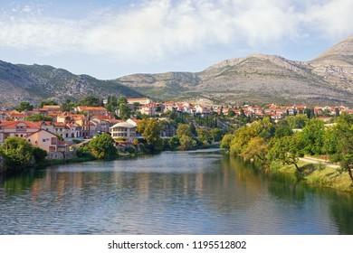 Picturesque landscape with town on river bank. Bosnia and Herzegovina, Republika Srpska. View of Trebisnjica river and Trebinje town, autumn