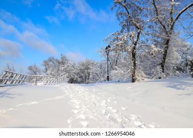 Picturesque landscape of winter park, covered with snow, with a beautiful lantern against the blue sky