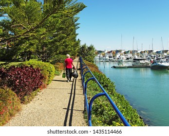 Picturesque Marina at Keppel Bay, waterfront walkway with guard rail, tropical water with boats, shrubs and blue sky background. Safe haven for sailing and cruising vessels. The Great Barrier Reef.