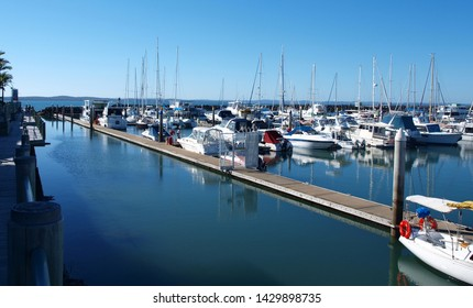 Picturesque Marina. Waterfront walkway with boats in tropical water with blue sky backdrop. Safe haven for sailing and cruising vessels.  Urangan Marina, Queensland, Australia.