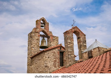 Picturesque mediaeval bell tower with cloudy sky background, Saint Felix Church, Laroque des Albères, South of France