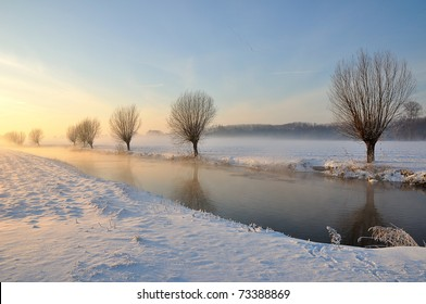 Picturesque and misty Dutch winter landscape with low sun, snow and partially ice on a narrow stream. Along the waterfront are bare willows. It is an award-winning photo of the municipality Drimmelen.