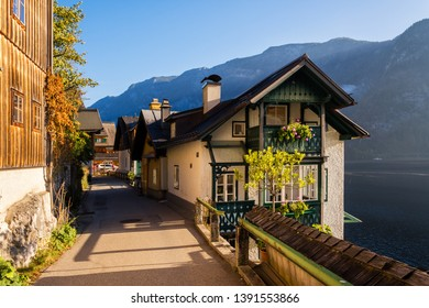 Picturesque morning scenery on Hallstatter with beautiful buildings on old street and alpine lake with mountains on background. Location: Hallstatt, Salzkammergut region, the Alps, Austria.