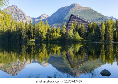 Picturesque mountain lake, surrounded by forest against the background of mountain peaks . National Park High Tatras. Famous resort Strbske Pleso. Slovakia. Picturesque summer mountain landscape.