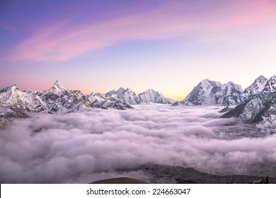 Picturesque mountain valley filled with curly clouds at sunset. Sacred Ama Dablam peak (6814 m) dominates on the left. Nepal, Himalayas. Canon 5D Mk II.