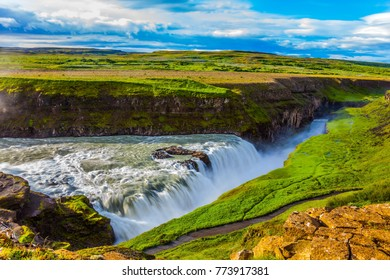Picturesque multi-colored tundra on a sunny summer day. The most picturesque waterfall in Iceland - Gullfoss on the Hvitau River. The concept of extreme and phototourism