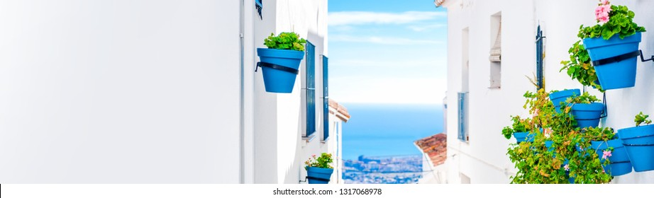 Picturesque narrow street of Mijas with blue flower pots on hillside houses facades Mediterranean sea. Andalusian white village. Costa del Sol Spain, wall copyspace for advertisement or your text