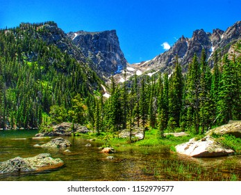 Picturesque nature photo of lake, mountains, blue sky and green trees.