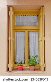 picturesque ocher painted window with potted small plants