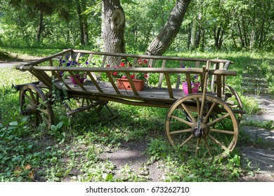 Picturesque old wooden cart with flowers in the park