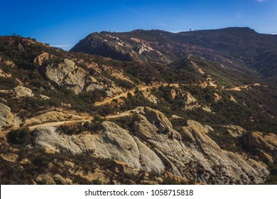 Picturesque overlook of Calabasas Peak Trail winding through the canyon with rock formations on a sunny day with blue sky and clouds, Calabasas Peak State Park, Calabasas, California