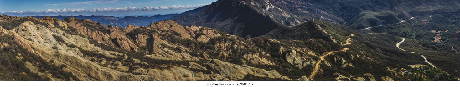 Picturesque panorama of Calabasas Peak Trail winding through the canyon with rock formations on a sunny day with blue sky and clouds, Calabasas Peak State Park, Calabasas, California