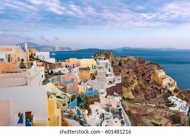 Picturesque panorama of Oia or Ia on the island Santorini, Byzantine Castle Ruins, white houses and church with blue domes, Greece.