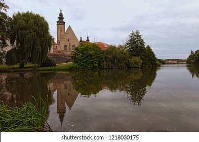 A picturesque park with a lake near the castle of Telc. Ancient buildings at the background. Summer landscape photo. A UNESCO World Heritage Site. Southern Moravia, Telc, Czech Republic.