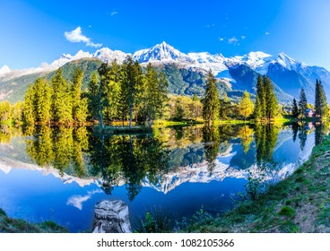Picturesque park in the mountain resort of Chamonix, at the foot of Mont Blanc. Snowy peaks of the Alps are beautifully reflected in the lake. Concept of active and ecotourism