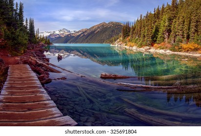 Picturesque path along turquoise mountain lake with a pine tree lined shore and snow capped mountains in the background