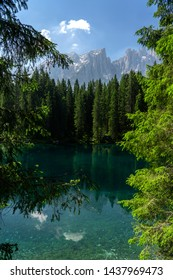Picturesque peaks of Dolomites mountains in reflection of crystal clear pond surrounded by coniferous forest. Lake of Caresse in Italy. Scenic place and famous touristic destination. Primeval nature