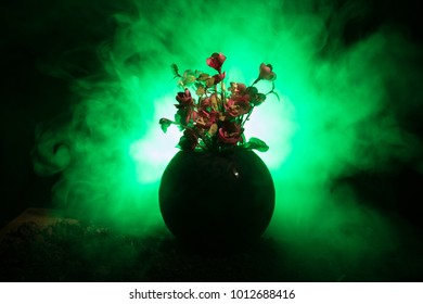 Picturesque purple spring flowers in glass vase standing in a row on a dark background with stars with light and fog. Flower concept. Dark decoration background