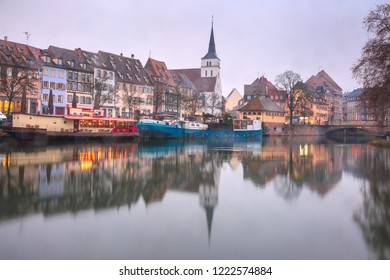 Picturesque quai des Pecheurs, Fisherman Wharf, and Protestant church of Saint Guillaume with mirror reflections in the river Ile during morning blue hour, Strasbourg, Alsace, France